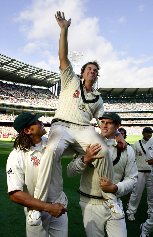 Australia's Shane Warne, center, is carried off the ground by team mates Andrew Symonds, left, and Matthew Hayden after they won the fourth Ashes cric...