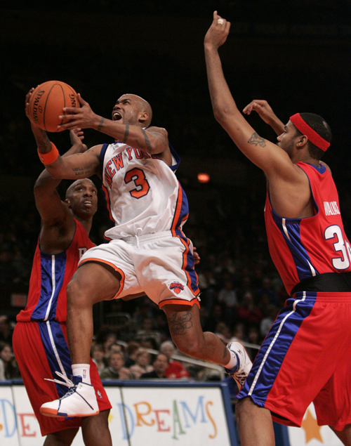 New York Knicks' Stephon Marbury, right, soars past Detroit Pistons' Chauncey Billups to score a basket during the second quarter in NBA basketball ac...