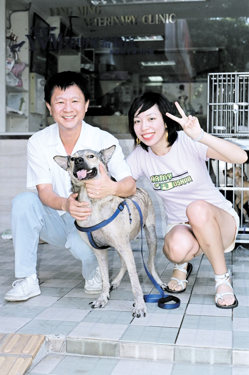 A woman, right, poses with her pet outside a veterinary clinic in Taipei.