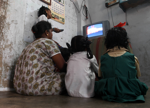 An Indian Tamil family watches color television at Samathuvapuram in Kancheepuram, around 80 kilometers south west of Chennai, India.