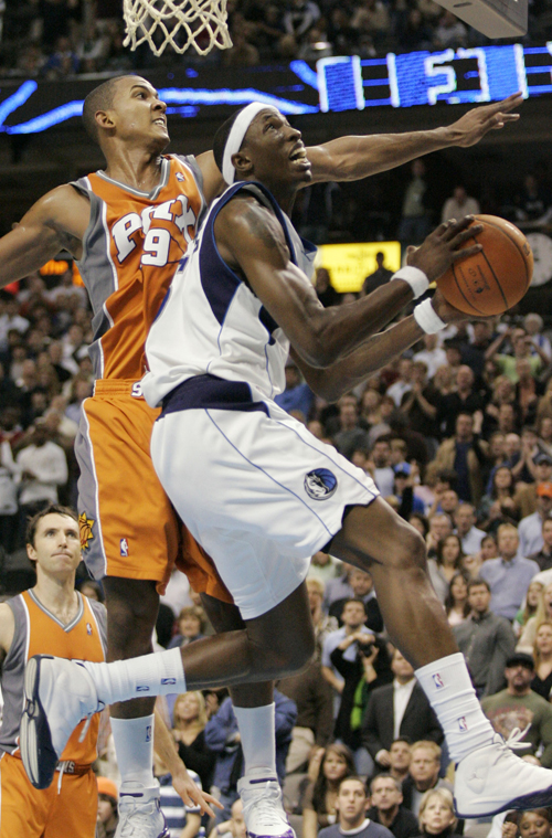 Dallas Mavericks forward Josh Howard, right, goes to the basket against Phoenix Suns guard Raja Bell in the second half of an NBA basketball game in D...