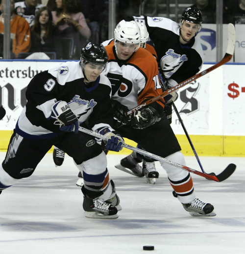 Tampa Bay Lightning's Eric Perrin, left, battles with Philadelphia Flyers' Ryan Potulny, center, for a loose puck during the first period of an NHL ho...
