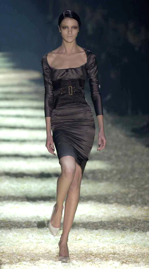 A model wears a black evening dress by Gucci.