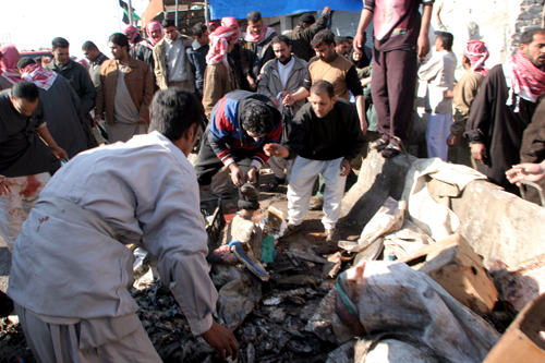 Iraqis go through the debris at a bomb explosion scene in Kufa, 160 kilometers south of Baghdad, Iraq yesterday.