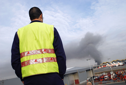 A man watches smoke rising above one of the parking lots of Madrid's Barajas airport in Spain after an explosion yesterday.