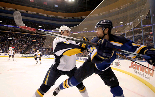 St. Louis Blues right winger Radek Dvorak, right, gets pushed into the boards by Buffalo Sabres right wing Ales Kotalik during their game in St. Louis...