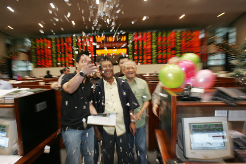 Filipino traders throw confetti as they celebrate in front of the electronic board at the closing of markets at the Philippines Stock Exchange in the ...