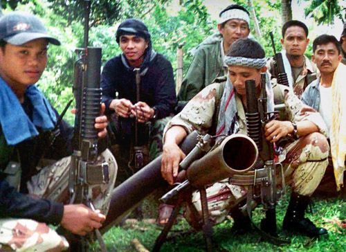 One of Abu Sayyaf leaders Khaddafi Janjalani, second from left, sits with fellow Abu Sayyaf rebels inside their jungle hideout in the Sulu province of...