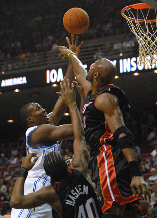 Orlando Magic center Dwight Howard, left, puts up a shot over Miami Heat forward Udonis Haslem, center, and Alonzo Mourning during the first half of t...