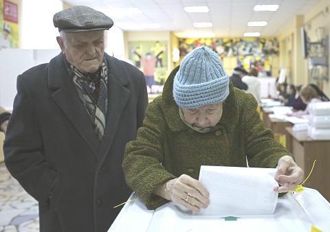 一對俄羅斯老年夫婦3月4日在莫斯科一個投票站為總統大選投票。(AP)