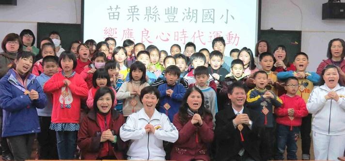 在校長的帶領下,豐湖國小師生大家伸出雙手,一起做出良心手勢,象徵「守護你我心中的良知 共創愛與和平心時代」。
