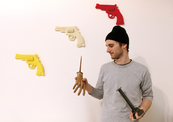 """The designer Kiel Mead in front of a wall of Sara Applebaum's guns made of felt, which are part of his Mead's exhibition at Present Company called """"Th..."""