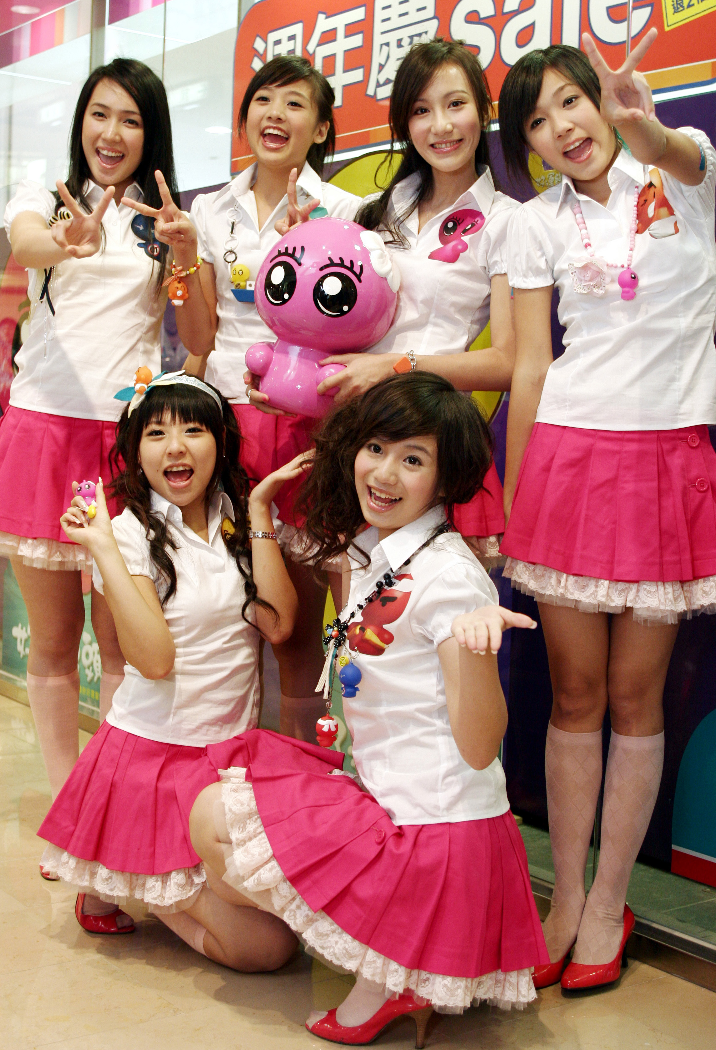 """Members of a girl group"""" Blackie"""" hold a figure called """" steamed bun """" to promote an anniversary sale held by Watsons Inc. on Oct. 04, 2006."""