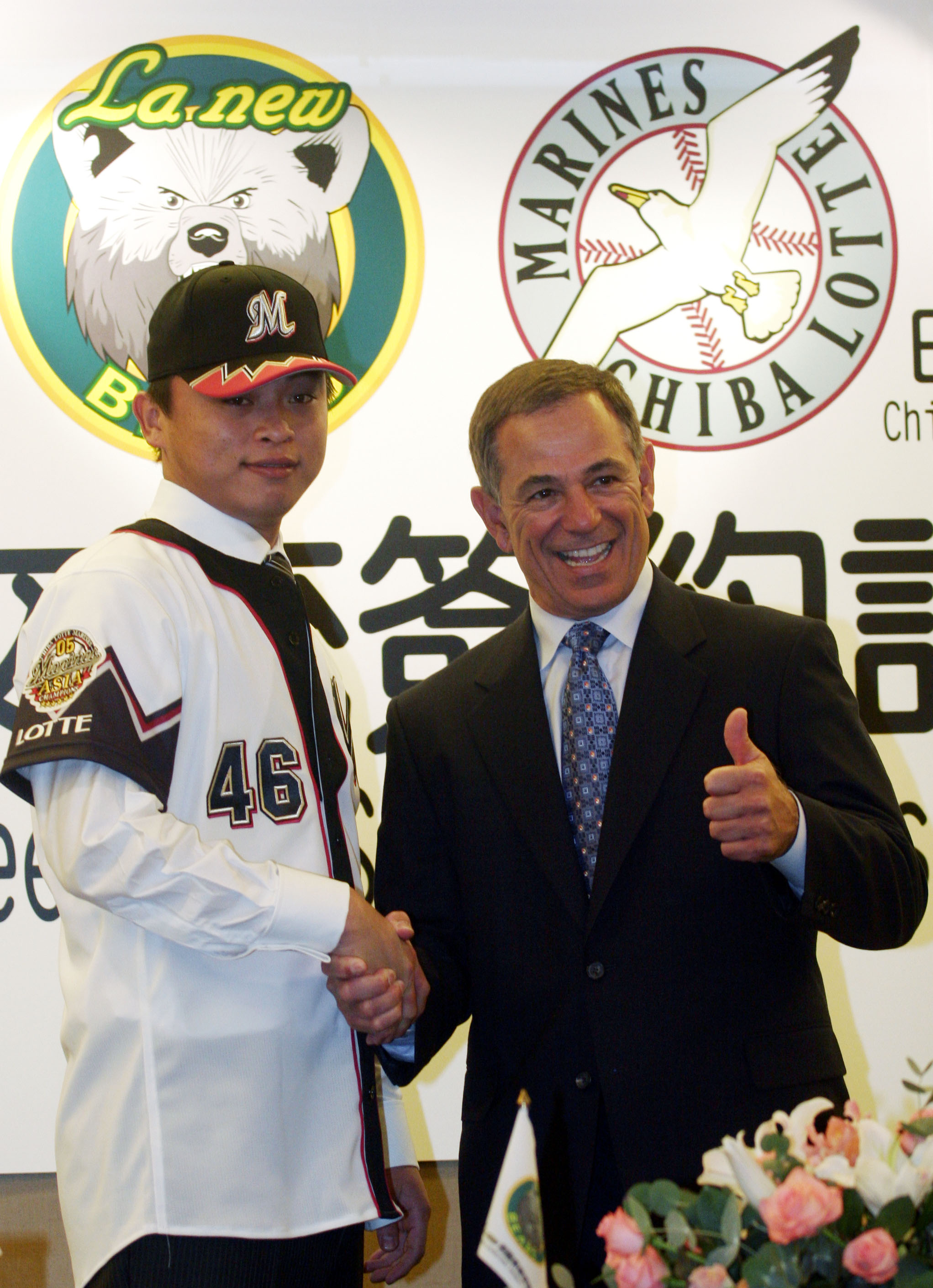 La New Bears, left, the lefty pitcher Wu Si-yo wears his new Japan's Chiba Lotte Marines jersey with Japan's Lotte Marines manager Bobby Valentine dur...