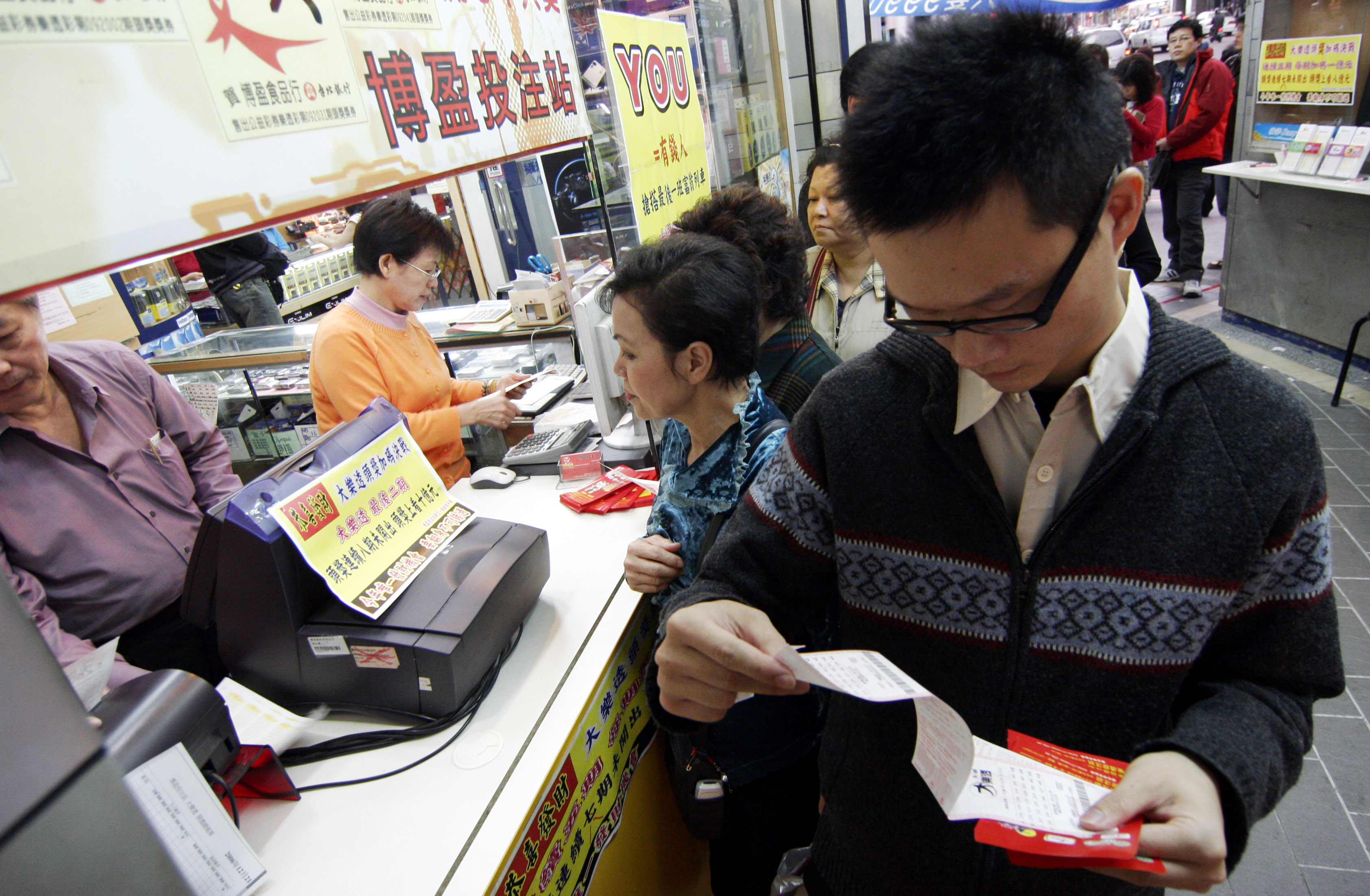 People queue up to buy lottery tickets at a famous lottery counter in Taipei, December 26, 2006. The lottery offers a top prize of at least 9 hundred ...