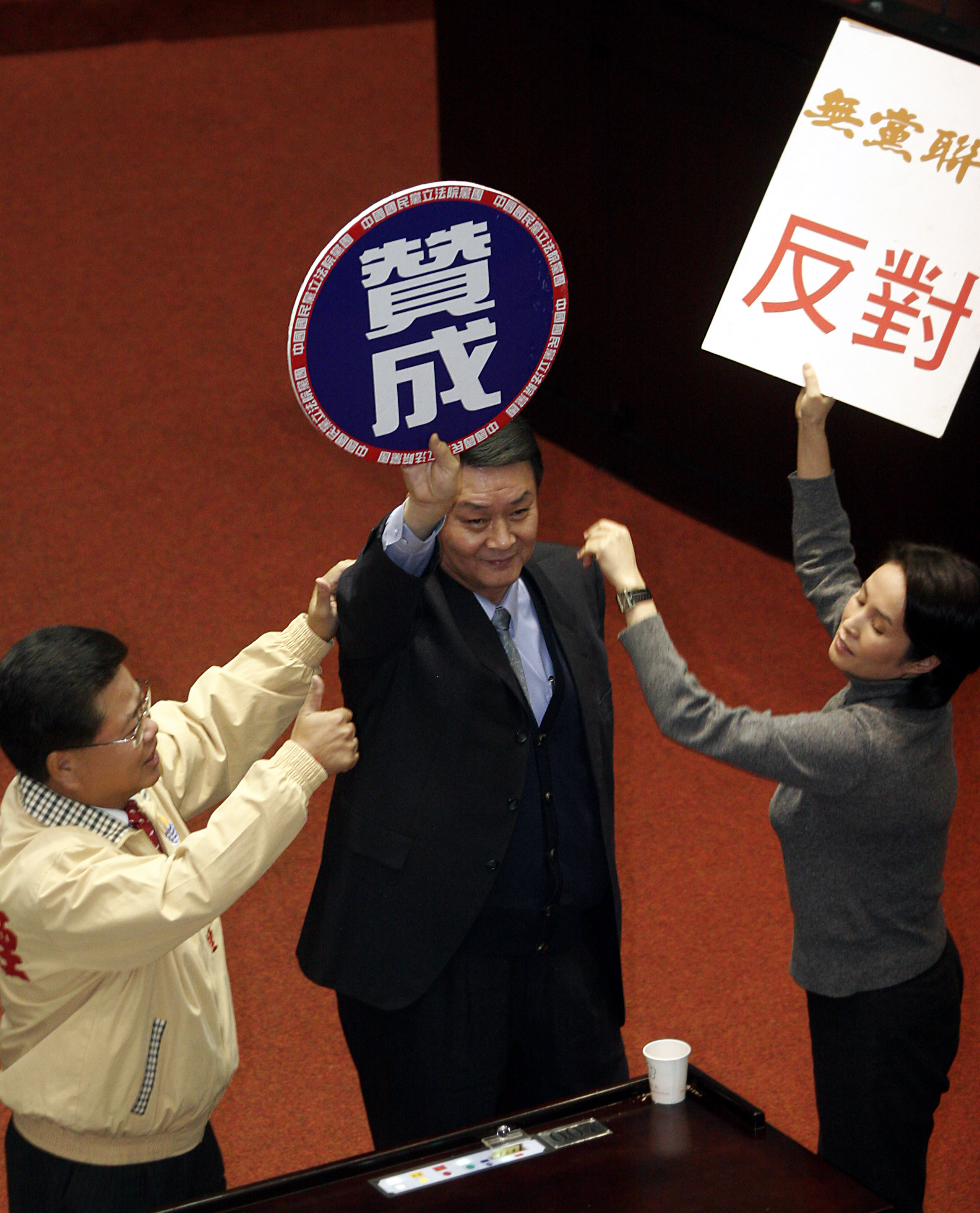 Opposition Nationalist Party lawmaker Tsai Chin-lung, center, holds a sign that reads 'Approve' during a vote on an arms package deal at the Legislatu...
