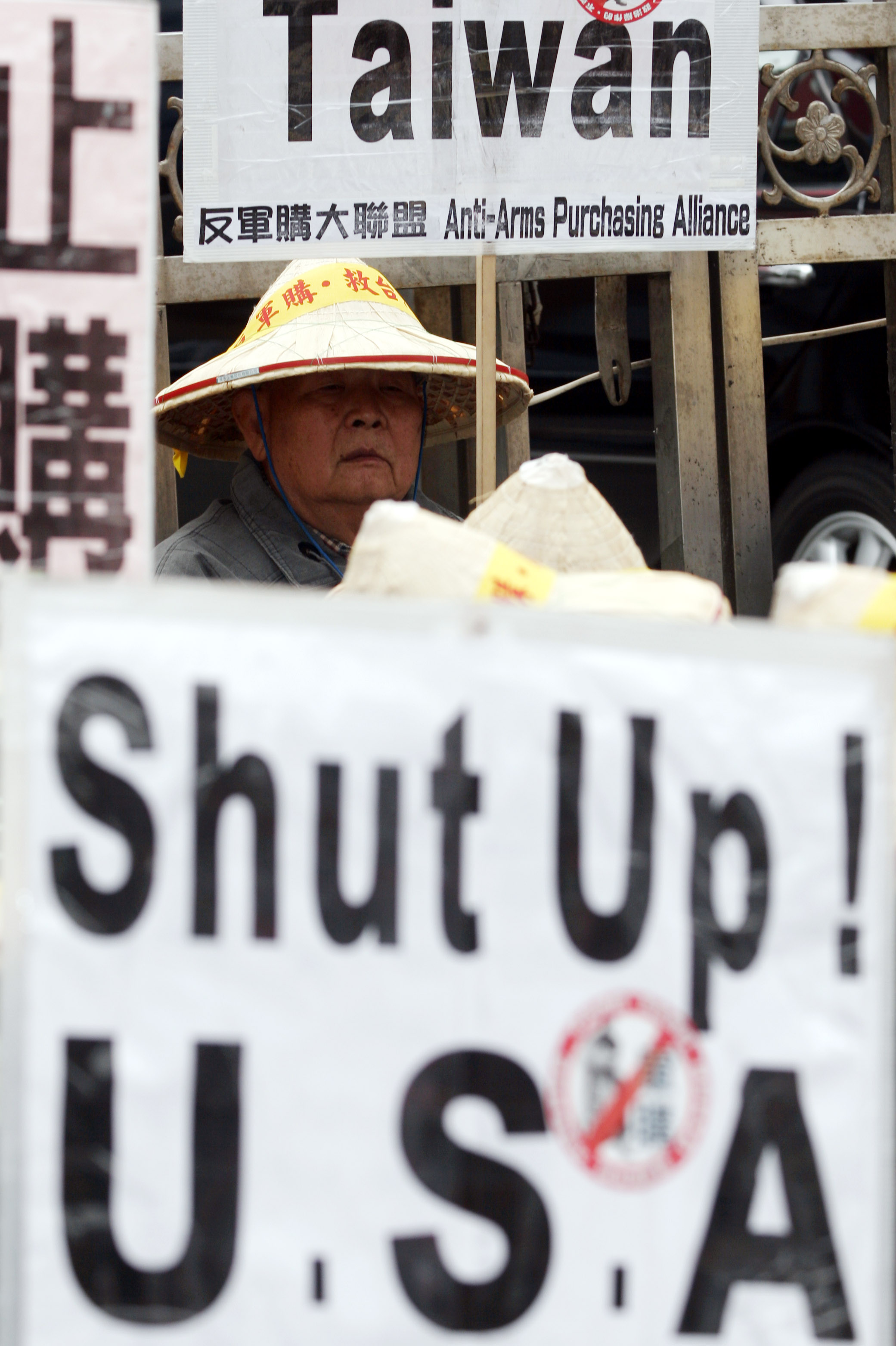 A protester holds a placard during a demonstration opposing the purchasing of weapons outside the Legislature, Friday, Dec. 29, 2006, in Taipei.