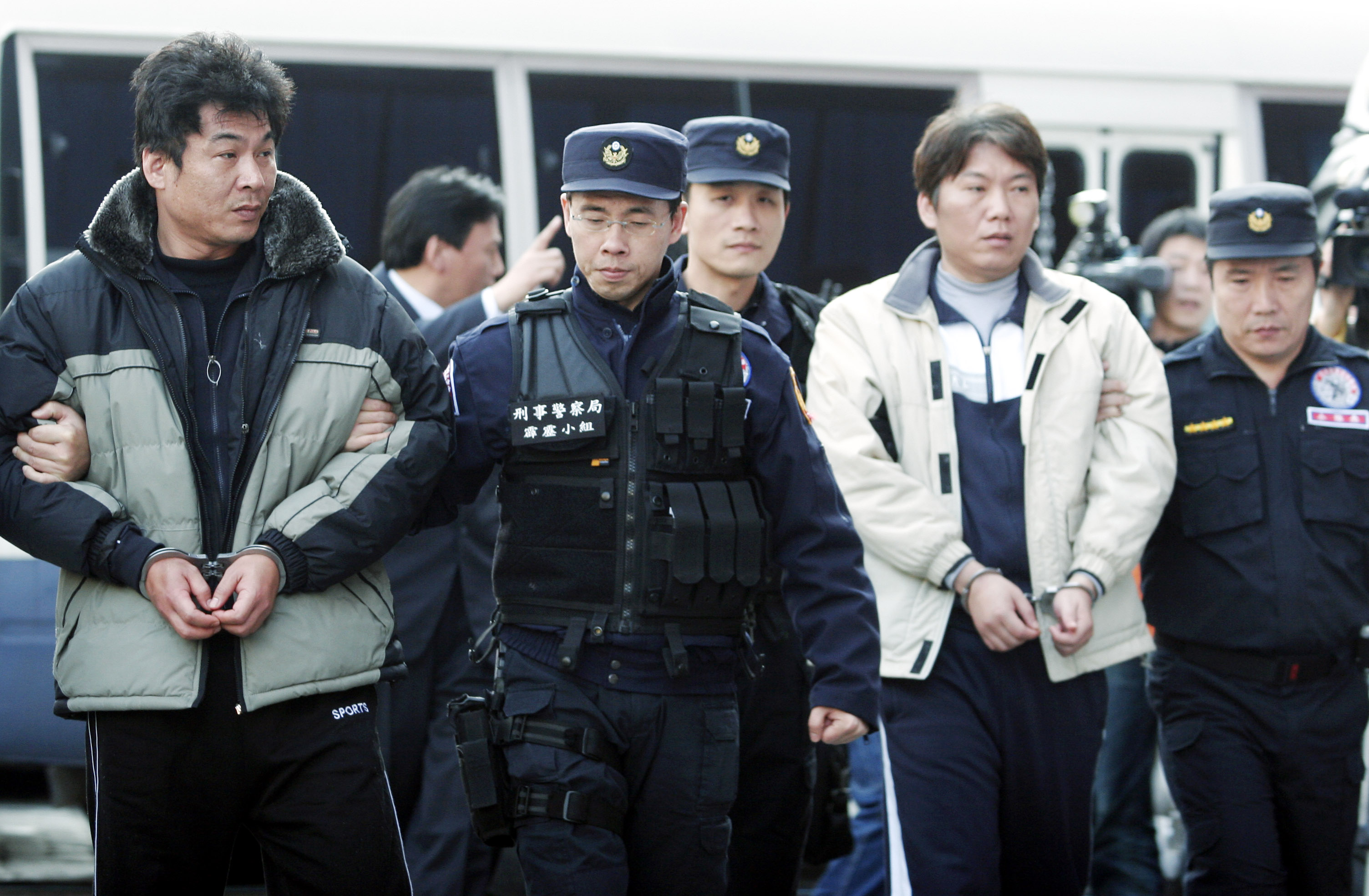 Armored car robbery suspects, Lee Han-yang, left, and his younger brother, Lee Chin-tsan return to Taiwan escorted by police at the Criminal Investiga...