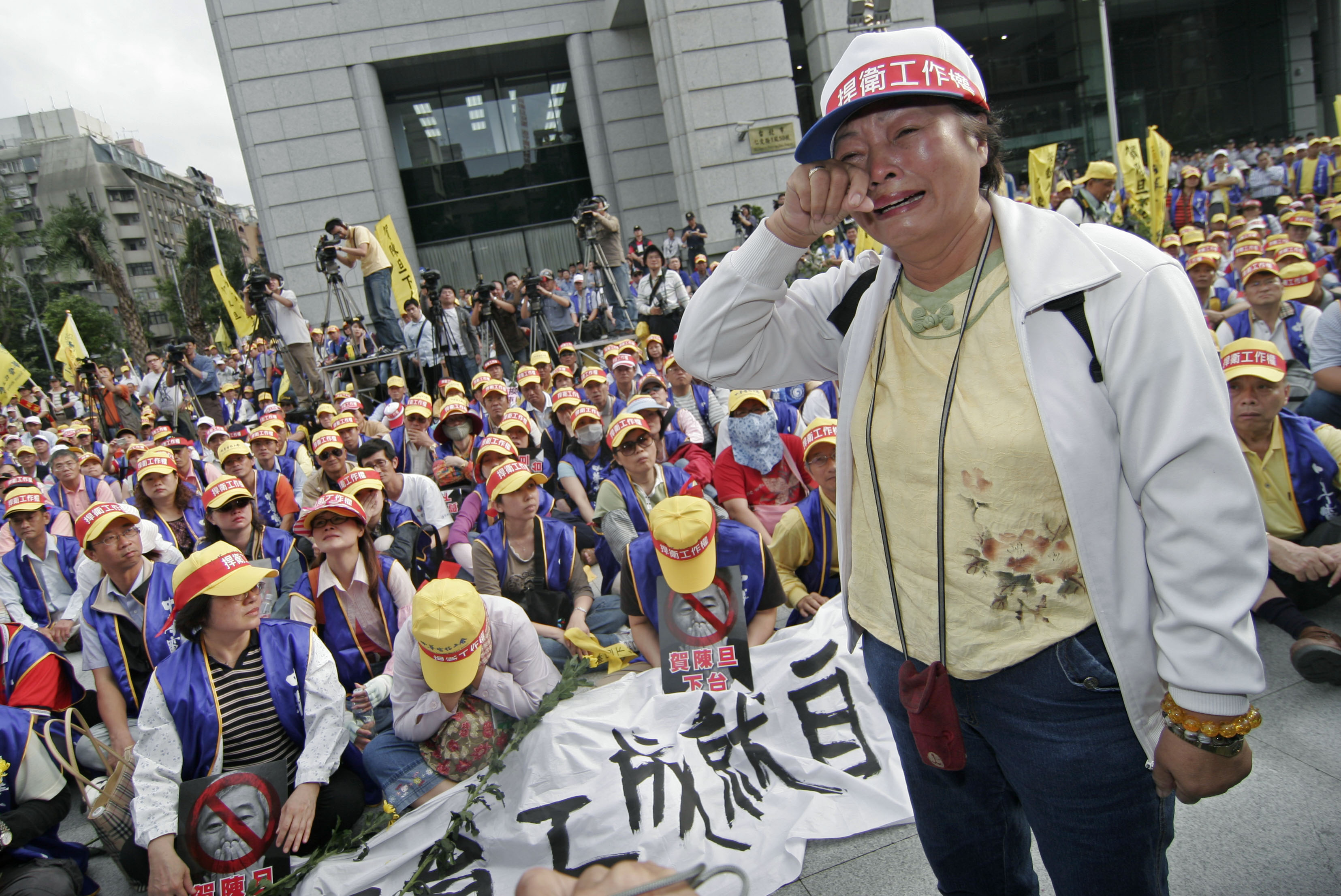 A Chunghwa Telecom union worker cries during a march to demand the resignation of the company's chairman Ho-Chen tan in front of the Ministry of Trans...