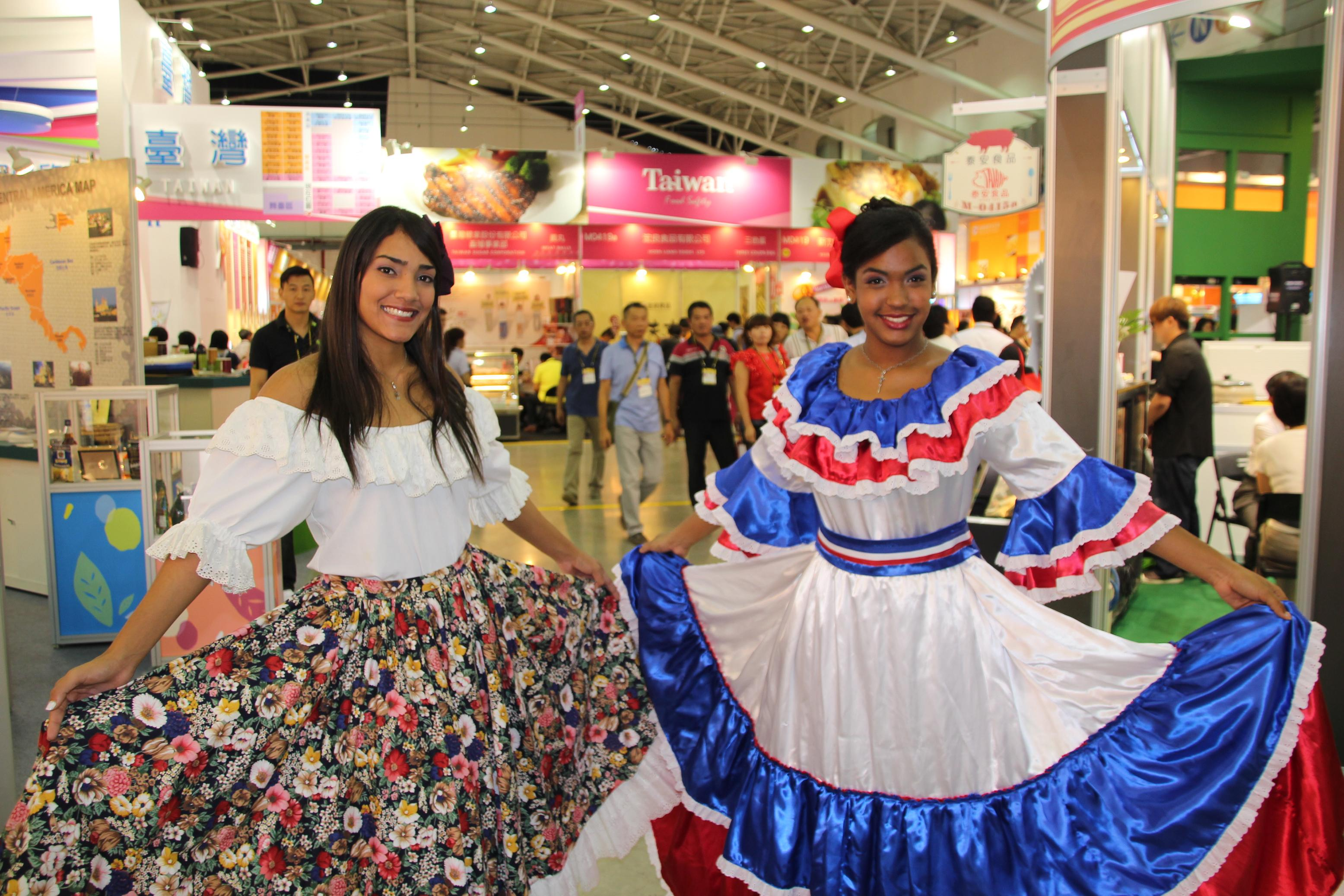 Dominican girls dressed in folkloric dance costume welcome visitors to the Dominican Republic booth at the 2015 Taipei International Food Show on Thur...