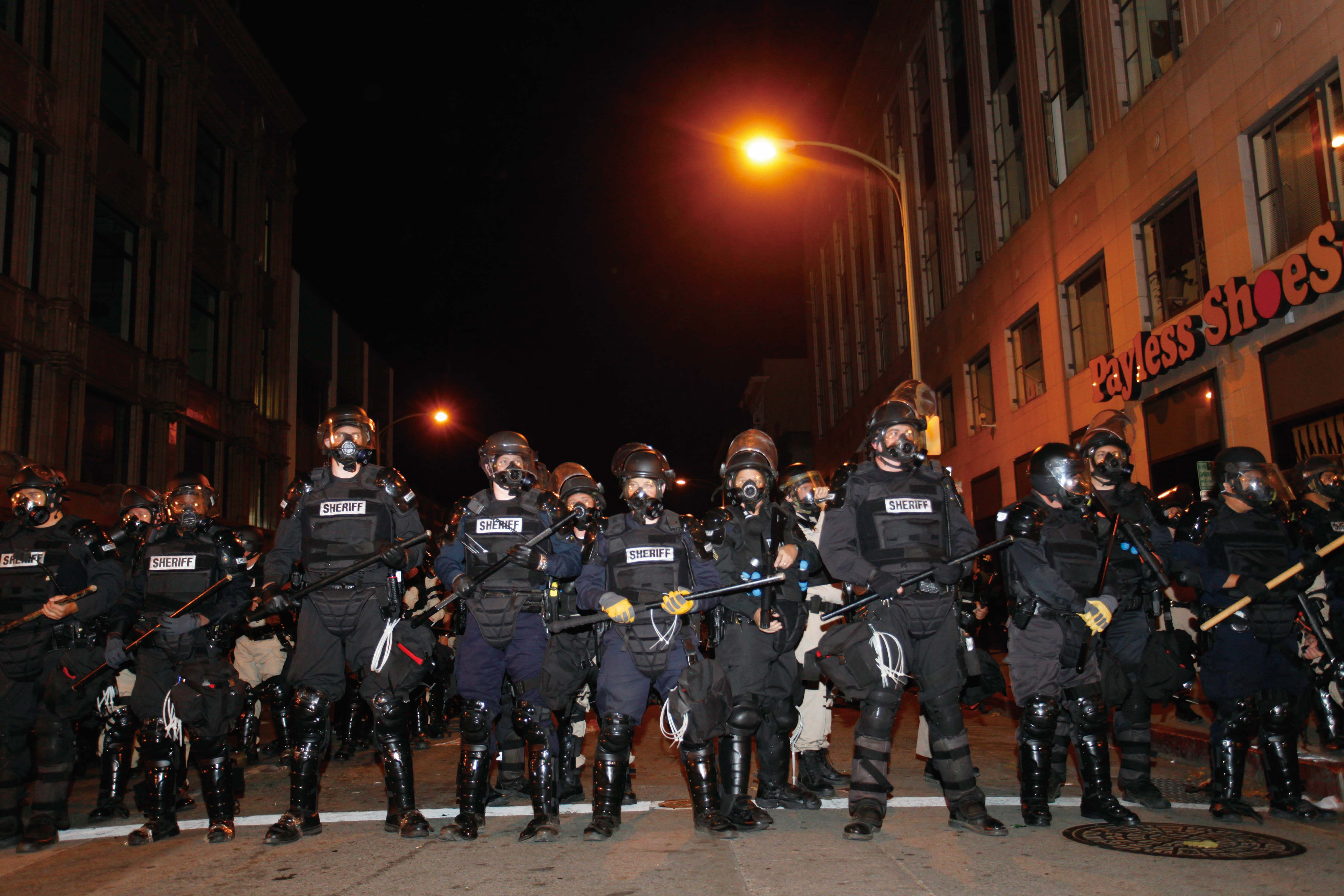 Police officers form a line to disperse the Occupy Oakland protesters who barricaded themselves on a street near the Oakland City Hall on November 3, ...