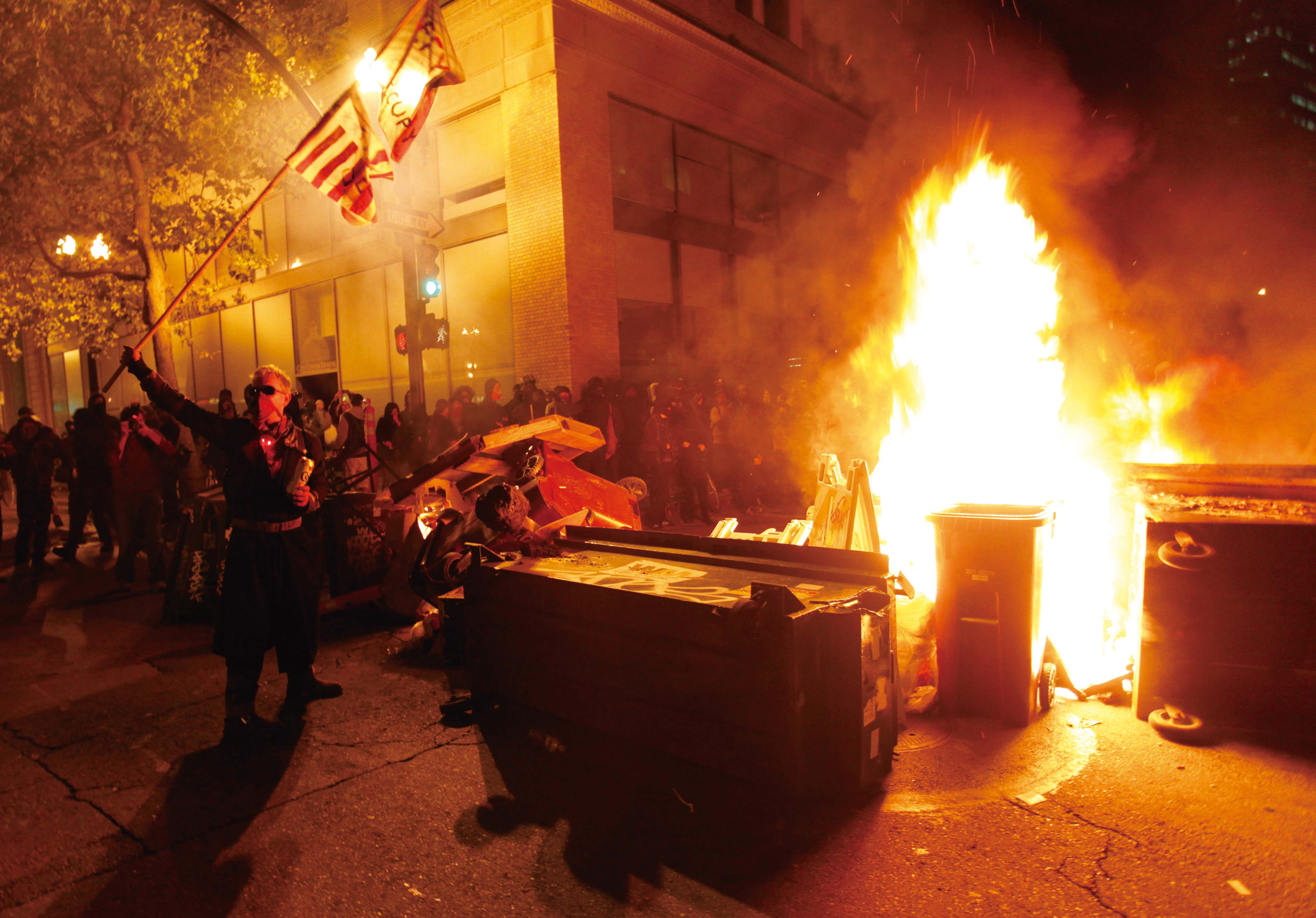 The Occupy Oakland protesters set a fire on trash to make a barricade as the police officers form a line to disperse the protesters on November 3, 201...