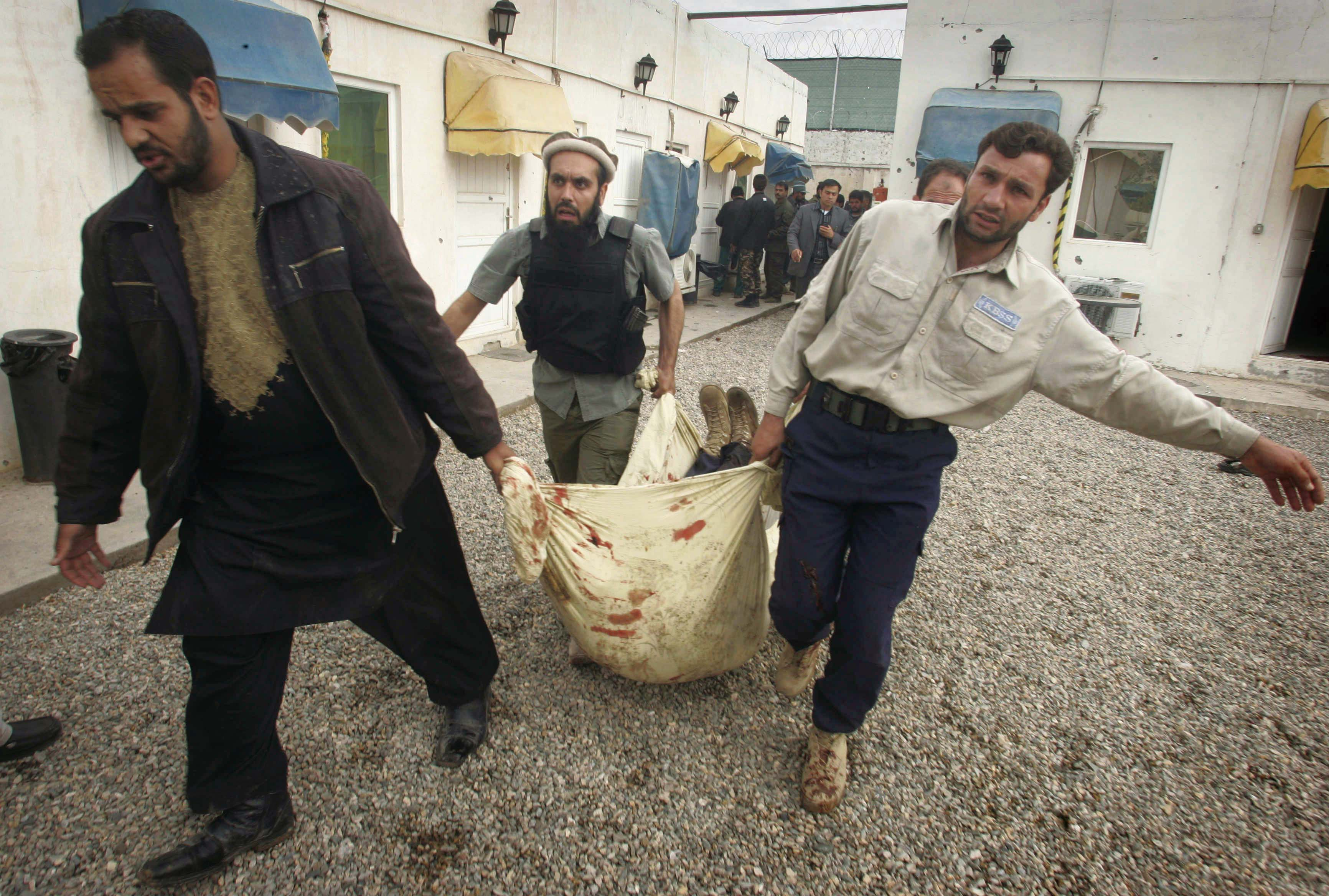 Afghans carry body of a security man, belonging to a private security company, who was killed in a gun battle with insurgents in Herat, west of Kabul,...