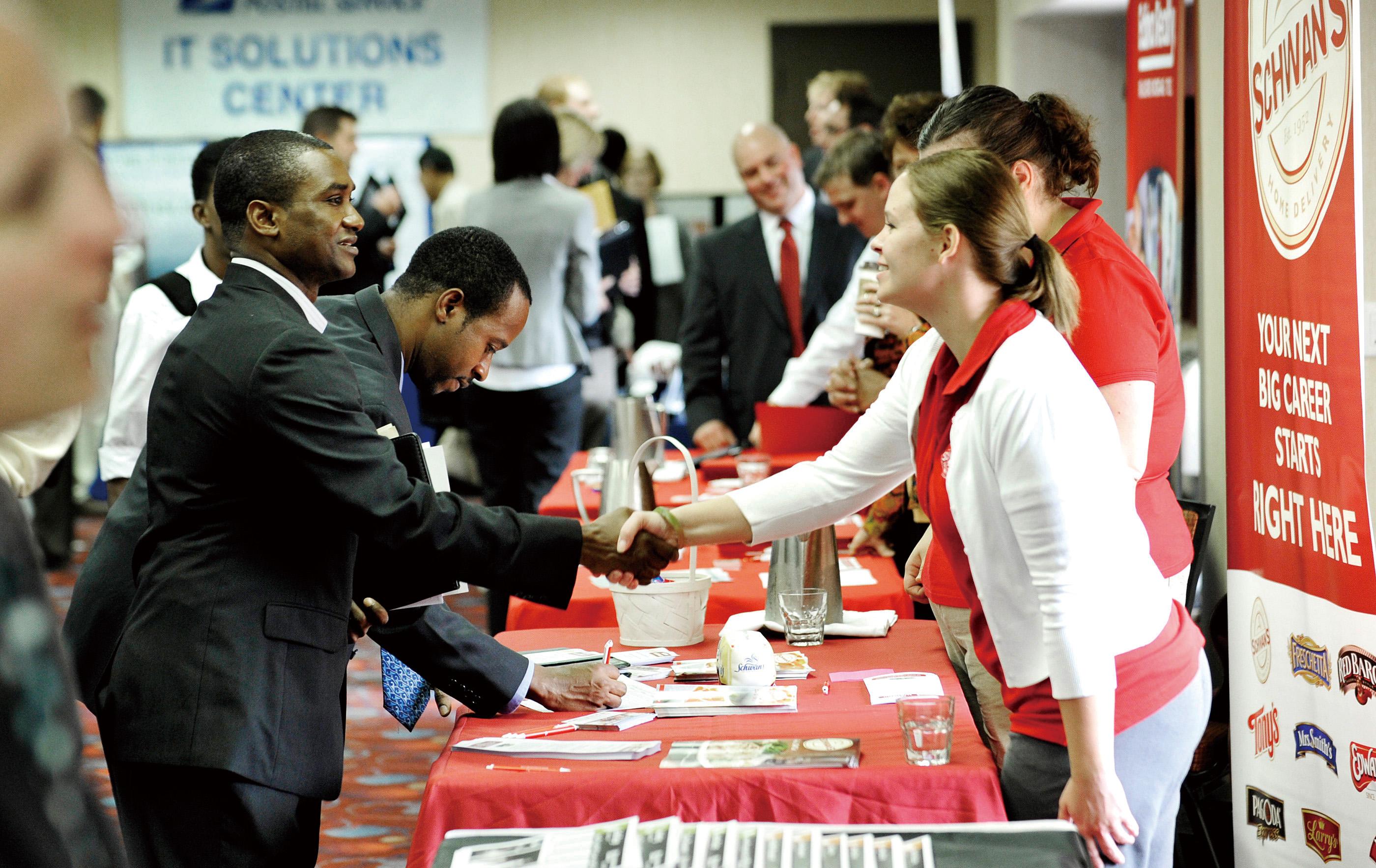 Job seekers visit the Minneapolis Career Fair held Wednesday, Nov. 2, 2011, in Bloomington, Minn. Fewer people applied for unemployment benefits last ...