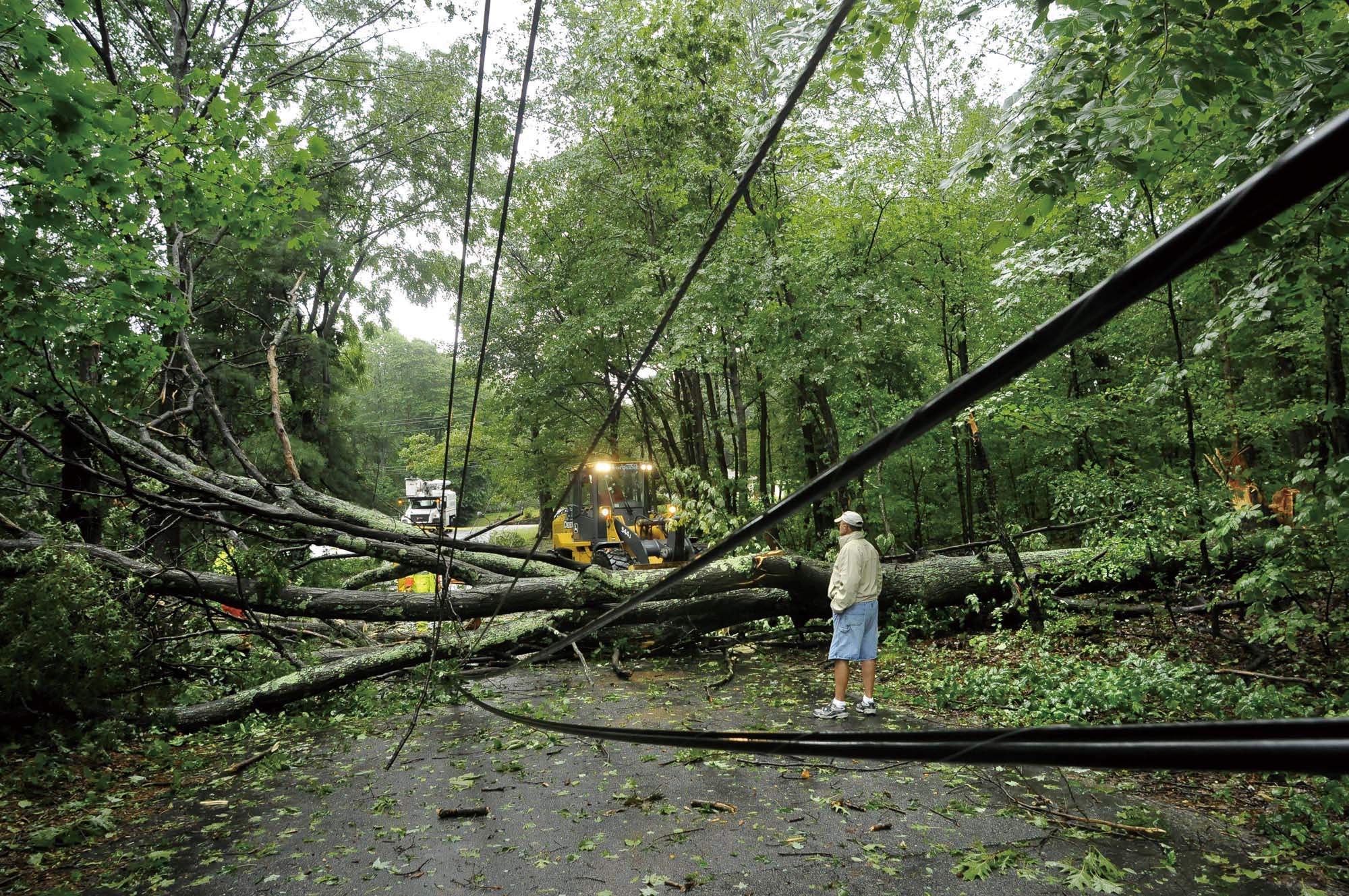 In this Aug. 28, 2011 file photo, a resident of Gover Road in Millbury, Mass., watches as crews work to clear a tree that knocked down power lines dur...
