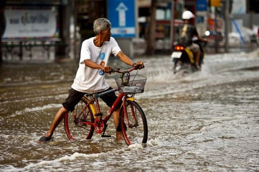 """A man rides his bicycle through floodwaters on the edge of downtown Bangkok, on November 4. Bangkok's well-protected centre is only at risk of """"minor""""..."""