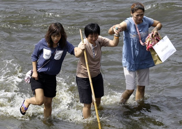 Thai women hold on to each other as they cross a flooded street at the Lad Phrao district in Bangkok, Thailand, Saturday, Nov. 5, 2011. Thailand's rec...