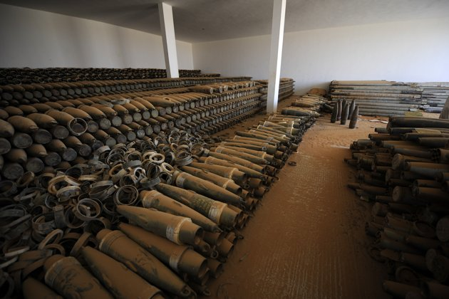 Piles of ammunition lie stored in a bunker, some 100km south of the Libyan city of Sirte. Crumbling jet fighters and rusted tanks, commanded by yes-me...