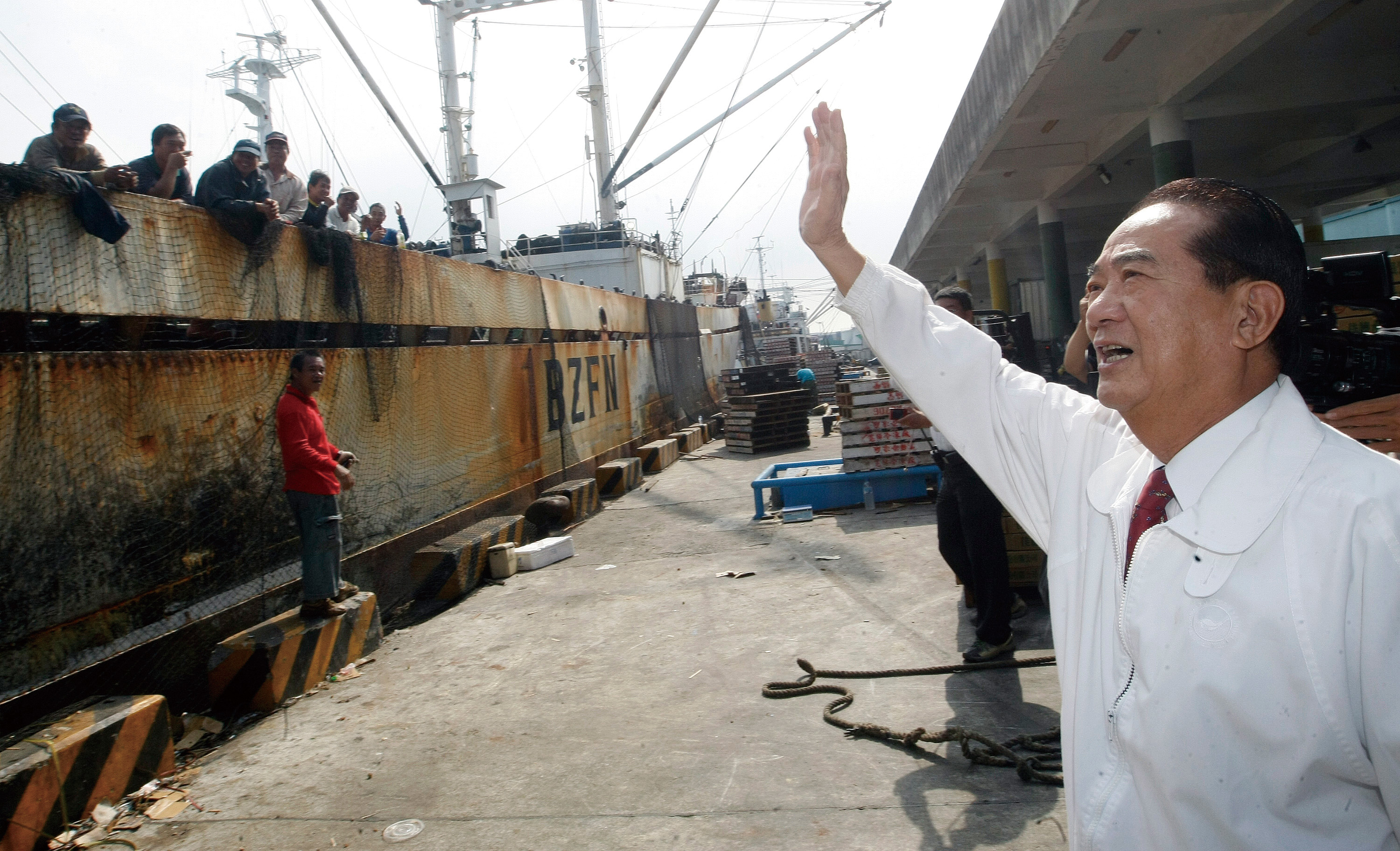 PFP chairman and presidential aspirant James Soong Friday visits Cianjhen Fishing Port in Kaohsiung and waves at the fishermen standing at the quaysid...