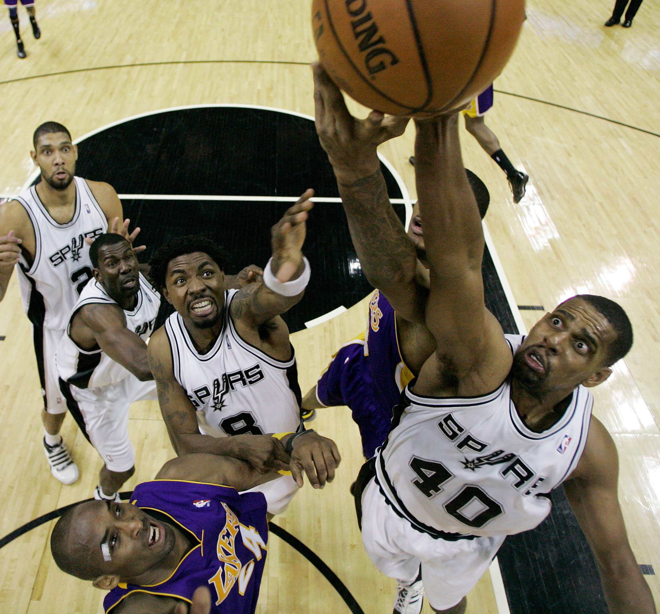 Los Angeles Lakers' Kobe Bryant (24) looks on as teammate forward Trevor Ariza, second from right, competes with San Antonio Spurs center Kurt Thoma...