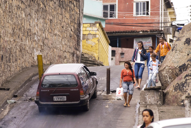 Pedestrians and a car pass by an alley blockade in this 2007 file photo of the Complexo do Alemao in the Favela de Grota, in Rio de Janeiro, Brazil.