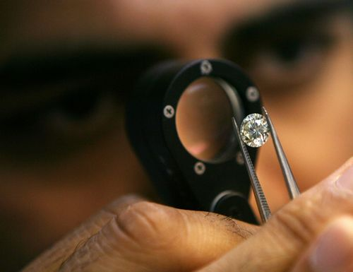 A diamond businessman  examines a diamond at a cutting and polishing factory in Surat in the western Indian state of Gujarat on March 3.