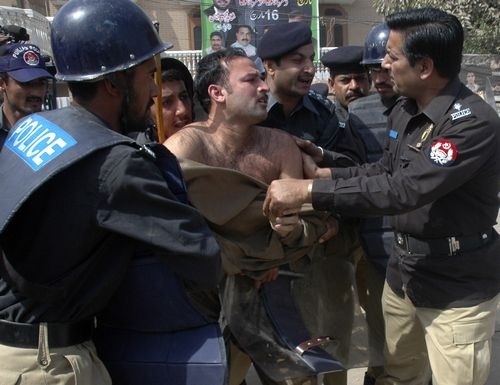 Pakistani policemen arrest an activist of the Pakistan Muslim League after government-banned protests in Multan, Pakistan yesterday.