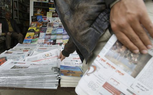 A resident buys newspapers from a kiosk in Baghdad, Iraq on Feb. 23.