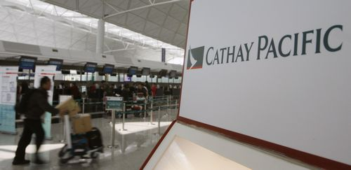 A passenger walks past a Cathay Pacific Airways self check-in machine at the Hong Kong Airport in Hong Kong yesterday.
