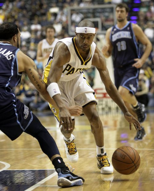 Indiana Pacers' T.J. Ford, center, dribbles around Utah Jazz's Deron Williams during their NBA game in Indianapolis, Indiana on Tuesday.