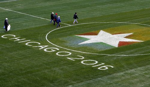 Workers walk on the field during a tour for International Olympic Committee members at Soldier Field, Chicago, Illinois on Sunday.