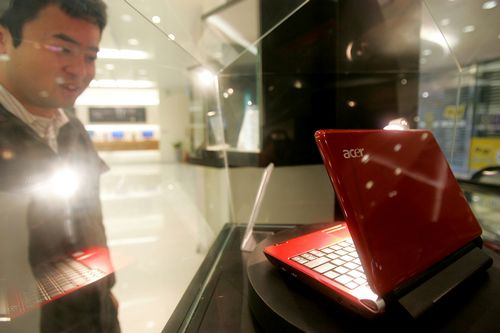 A visitor looks at an Acer Inc. Aspire One laptop computer on display in the showroom at the company's headquarters in Hsinchu, Taipei county, Taiwan ...