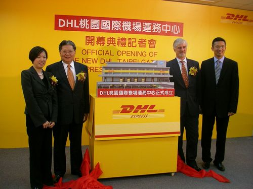 Jerry Hsu, second left, and Stephen Fenwick, second right, stand next to a model of the DHL Taipei Gateway in Taoyuan yesterday.