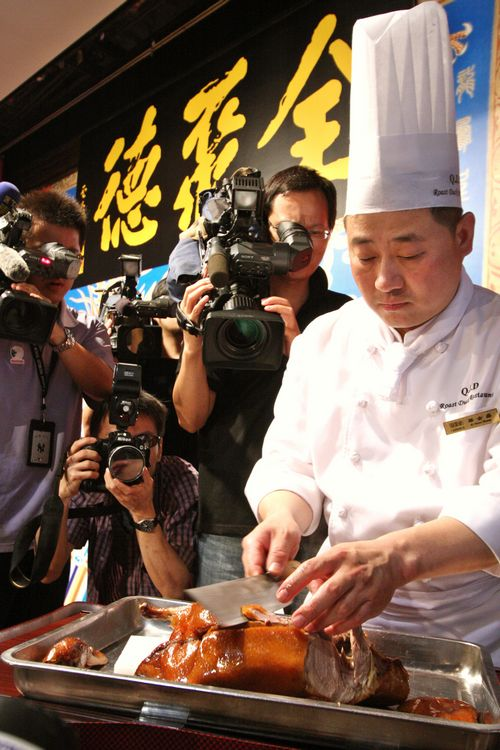 A chef from the famous Chinese Quanjude restaurant demonstrates the way to cut the famous Chinese cuisine Beijing Duck during a news conference yester...