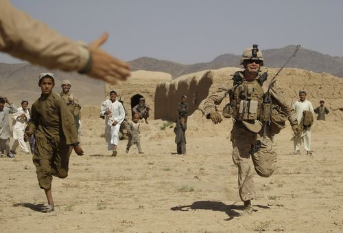 U.S. Marine 2nd Lt Malachi Bennett from Tampa, Florida, of the 2nd MEB, 2nd Battalion, 3rd Marines competes in a foot race against an Afghani boy insi...