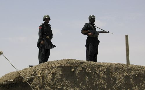 Pakistani paramilitary soldiers observe an area from the rooftop of a checkpoint at Abbato Karaz village near Chaman, Pakistan, along the southwest Af...