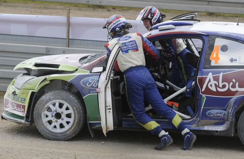 Finland's Jari-Matti Latvala, left, and with co-driver Miikka Anttila push their Ford Focus RS WRC on the track after it broke down during the last sp...