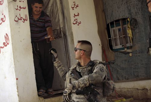 An Iraqi youth serves tea to U.S. Army Spc. Adam Steele of 1st Battalion, 5th Infantry Regiment, during a patrol in Baqouba, Iraq on Monday.