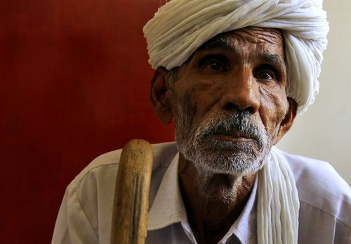 Zile Singh, an elderly villager, waits to file a case against his nephew who allegedly stole his land, at a courtroom in Jhajjar, on the outskirts of ...