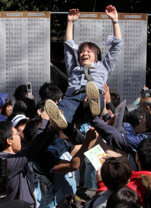 A successful applicant is tossed in the air by current students at The University of Tokyo in Tokyo, Japan on March 10.
